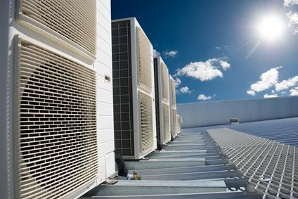 Air conditioner units on a roof of industrial building with blue sky and clouds in the background.
